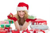 Woman in santa hat laying on the floor while holding gifts — Стоковое фото