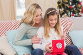Daughter opening christmas gift with mother — Stock Photo