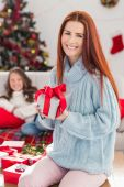 Festive mother holding a gift — Stock Photo