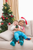 Cute boy and baby brother on couch at christmas — Foto de Stock