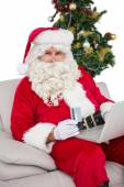 Santa shopping online on the couch — Stock fotografie