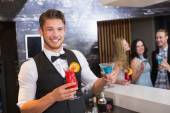 Handsome barman smiling at camera holding cocktails — Stock Photo
