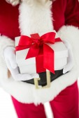 Santa claus holding a present — Stock Photo