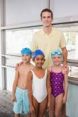 Swimming coach with his students poolside — Stock Photo