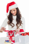 Happy brunette in santa hat packing gifts — Stok fotoğraf