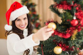 Festive brunette decorating a christmas tree — Stock Photo