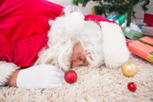 Exhausted santa resting on the rug  — 图库照片