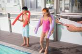 Swimming coach holding clipboard poolside — Stock Photo
