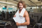 Handsome trainer with clipboard in gym — Stockfoto