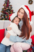 Festive mother and daughter hugging on the couch  — Foto Stock