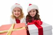 Festive little girls smiling at camera holding gifts — Fotografia Stock