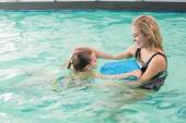 Happy mother and daughter in the swimming pool — Foto Stock