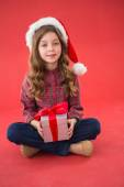 Happy little girl in santa hat holding gift — Stockfoto