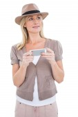 Happy blonde in trilby holding phone — Stock Photo