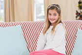 Cute little girl sitting on couch — Stock Photo