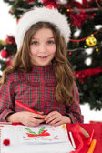 Festive little girl drawing pictures — Stock Photo