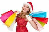 Excited blonde in santa hat holding shopping bags — Stock Photo