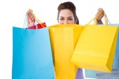 Happy brunette opening shopping bags — Stock Photo