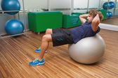 Man doing abdominal crunches on ball — Stockfoto