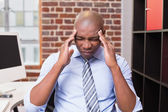 Businessman with severe headache in office — Stock Photo