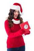 Disappointed brunette opening christmas gift — Stock Photo