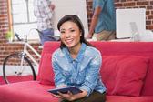 Woman using digital tablet on couch — Stock Photo