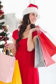 Bruneta v červených šatech drží nákupní tašky — Stock fotografie