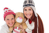 Mother and daughter holding teddy bear — Stock fotografie