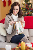 Brunette opening a gift on the couch at christmas — Stock Photo