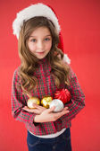 Festive little girl smiling at camera holding baubles — ストック写真