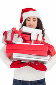Stressed brunette in santa hat holding pile of gifts — Стоковое фото