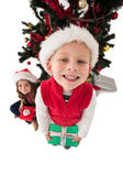 Festive little siblings smiling at camera holding gifts — Stock Photo
