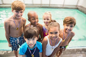 Cute swimming class smiling poolside with medals — Stock Photo