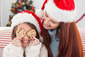 Festive mother and daughter on the couch with cookies — Stock Photo