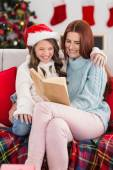 Festive mother and daughter reading on the couch — Zdjęcie stockowe