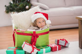 Cute little girl sitting in giant christmas gift — Stock Photo