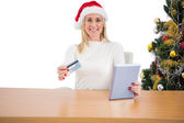 Festive blonde shopping online with tablet pc — Stock Photo