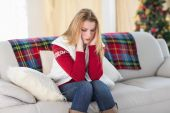 Woman with headache sitting on sofa — Stock Photo
