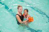 Cute little girl learning to swim with coach — Stockfoto
