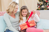 Cute little girl sitting on couch opening gift with mum — Zdjęcie stockowe