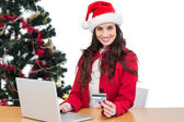 Festive brunette shopping online with laptop — Stock Photo