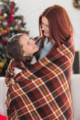 Festive mother and daughter wrapped in blanket — Stock fotografie