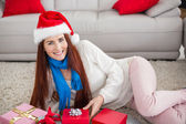 Festive redhead smiling at camera with gifts — ストック写真