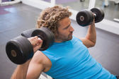 Man exercising with dumbbells in gym — 图库照片