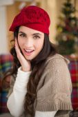 Surprised brunette on the couch at christmas  — Stock Photo