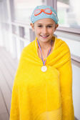Cute little girl standing poolside wrapped in towel — Stock fotografie