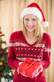 Festive pretty blonde woman offering gift — Stock Photo