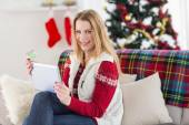 Cute blonde sitting on couch holding credit card and tablet — Stock Photo