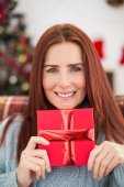 Festive redhead with gift on the couch — Stock Photo