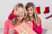 Little girl hiding gift from mother — Stock Photo